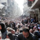 Refugees wait in line to receive food aid distributed in the Yarmouk camp on January 31, 2014 in Damascus, Syria. (United Nation Relief and Works Agency - UNRWA)